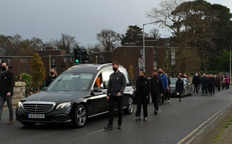 The hearse bearing the tri-colour draped coffin of Donal Ó Sé, flanked by a republican guard of honour, making the journey from Donal's home to Milltown Church.
